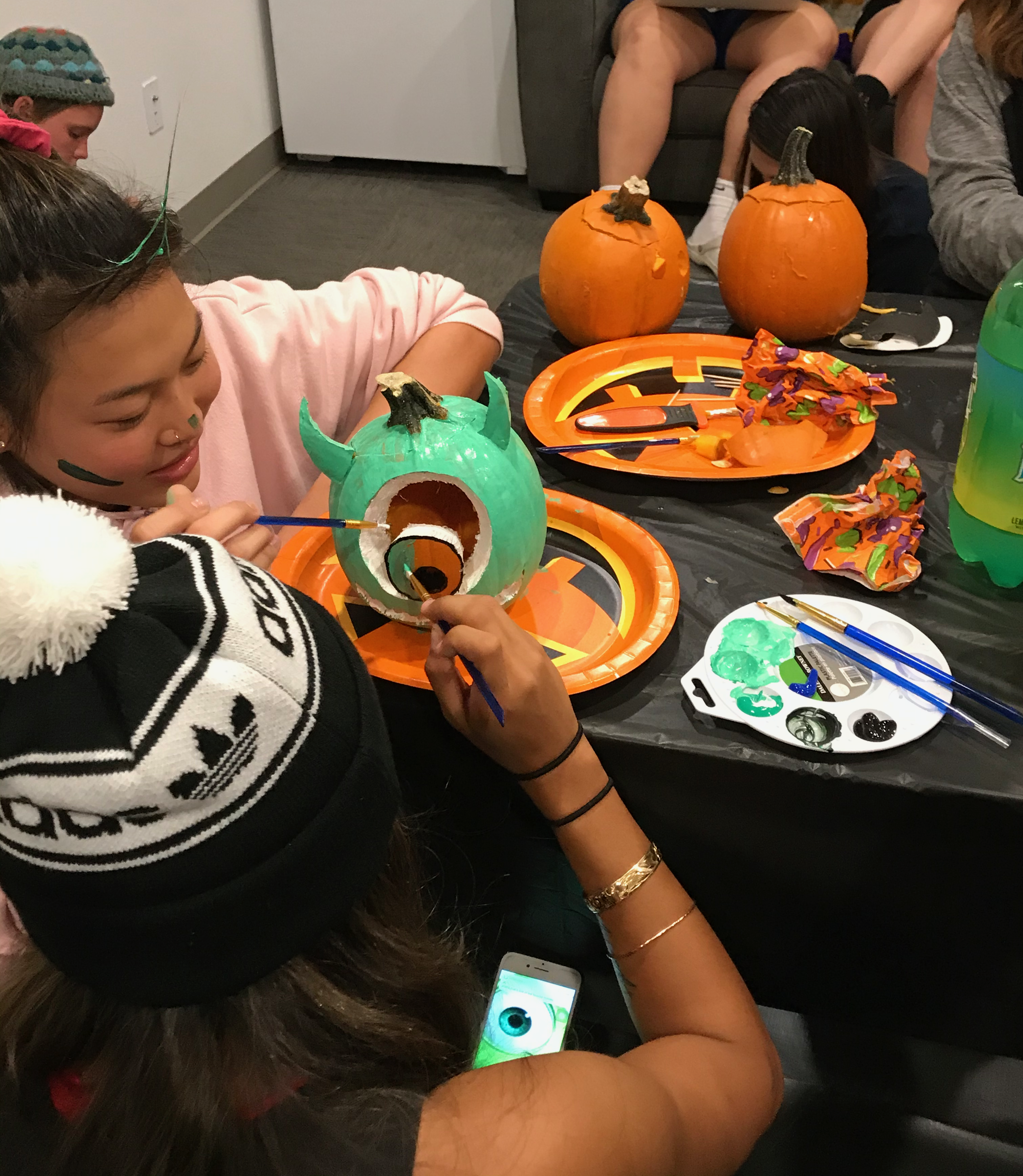 Two residents collaborating to finish decorating a pumpkin