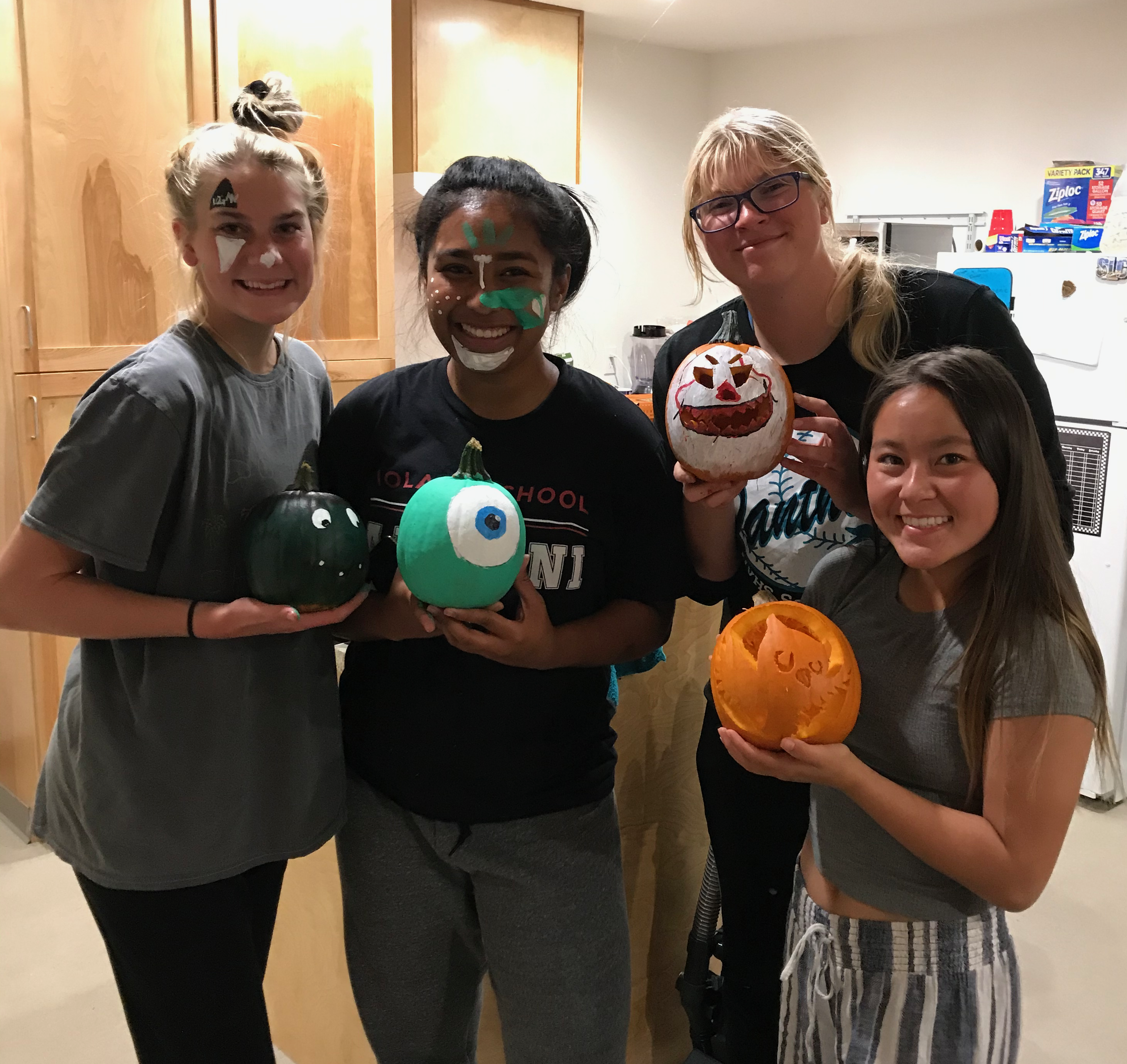 Four residents and four decorated pumpkins