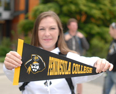 Woman Holding Peninsula College Pennant