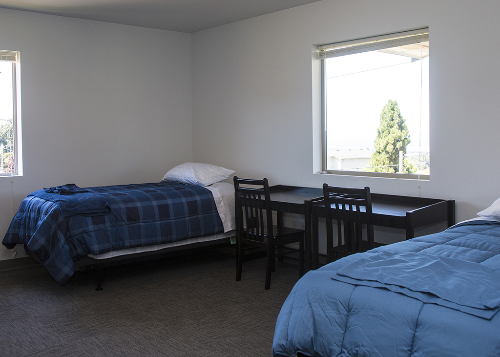 A photo of the bedroom, showing two single beds, two desks, and two big windows.